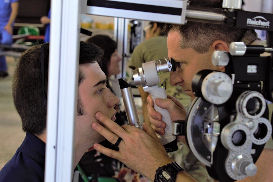 Maj. Joshua Metzger, optometrist, 127th Medical Group, Selfridge Air National Guard Base, Mich., examines a patient during Innovative Readiness Training Appalachian Care 2019 at Wise County Fairgrounds, Wise, Va., Aug. 18, 2019. Appalachian Care Innovative Readiness Training 2019 takes place Aug. 16-29, 2019, to care for the medically underserved communities of Wise, Virginia while simultaneously conducting deployment and readiness training for military personnel. Innovative Readiness Training is the only hands-on training opportunity authorized to operate within the U.S. During Appalachian Care IRT 2019, medical operations will be staged at one physical location at Wise County Fairgrounds. The Appalachian Care IRT 2019 team provides medical, dental, optometry and veterinary care to assist local health and municipal authorities in addressing underserved and unmet community health and civic needs. Units also conduct critical mission training and logistical movement in order to simulate hands-on deployment readiness operations and health care delivery in the time of crisis, conflict or disaster. (Air National Guard photo by 1st Lt. Andrew Layton)