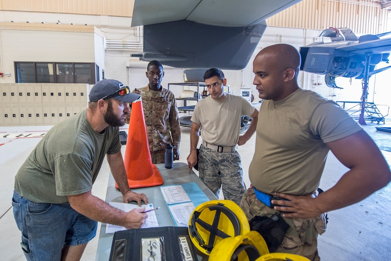 Members of the 727th Special Operations Aircraft Maintenance Squadron go over the task list to hoist an engine into a CV-22 Osprey at Cannon Air Force Base, N.M, Aug. 13, 2019. The process of replacing the engine took the team of three 25 minutes. (U.S. Air Force Photo by Senior Airman Vernon R. Walter III)