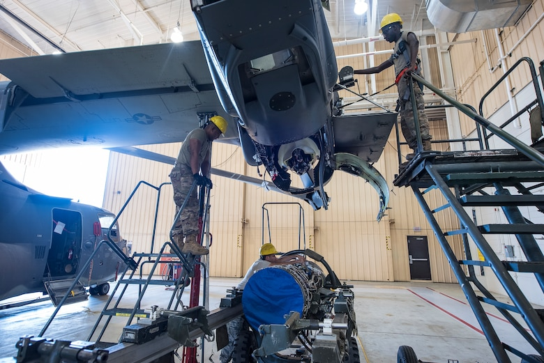 Members of the 727th Special Operations Aircraft Maintenance Squadron guide a CV-22 Osprey engine into position to be hoisted into the aircraft at Cannon Air Force Base, N.M, Aug. 13, 2019. The process of replacing the engine took the team of three 25 minutes. (U.S. Air Force Photo by Senior Airman Vernon R. Walter III)