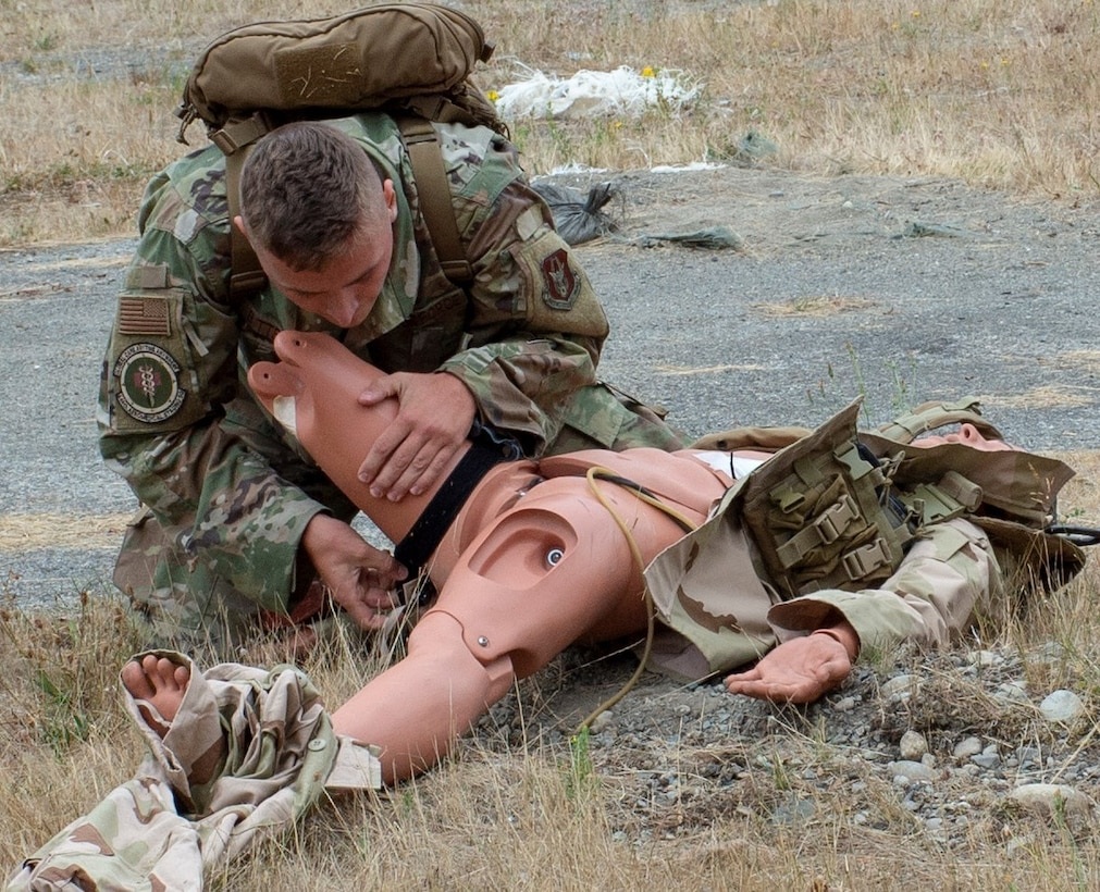 U.S. Air Force Staff Sgt. Connor Bitterman applies a tourniquet to a simulated casualty during a tactical combat casualty care (TCCC) class for exercise Tropic Halo 2019 at Joint Base Lewis-McChord in Tacoma, Wash., Aug. 7, 2019. Tropic Halo is designed to enhance Operational Hospital Support Unit Bremerton's medical and mission capabilities on several levels: increase TCCC and trauma nurse core course readiness rates while minimizing overall training costs; promote intra-service cohesion with collaborative training in a joint service environment and leverage Navy and Air Force command assets to generate better training opportunities. (U.S. Navy photo by Mass Communication Specialist 1st Class Ryan Riley)