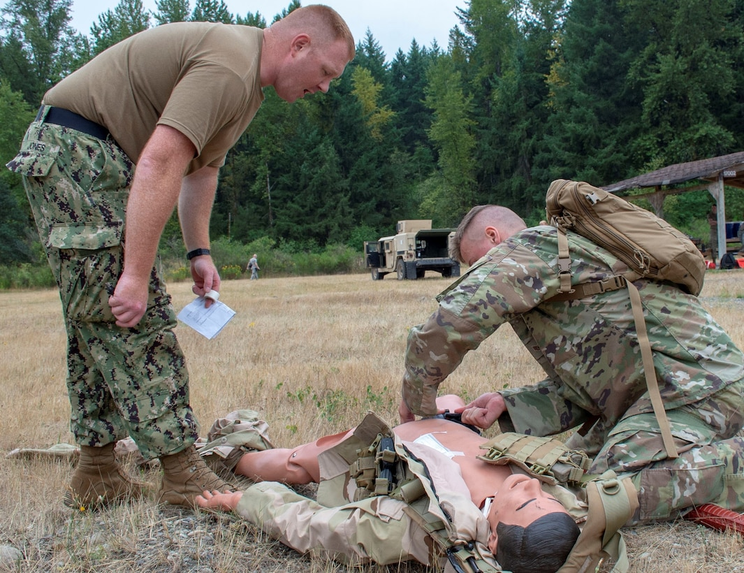 Hospital Corpsman 1st Class Brian Jones, an instructor assigned to Navy Reserve Navy Medicine Education and Training Command and selected for the rank of chief, evaluates Air Force Staff Sgt. Connor Bitterman tending to a simulated casualty during a tactical combat casualty care (TCCC) class for exercise Tropic Halo 2019 at Joint Base Lewis-McChord in Tacoma, Wash., Aug. 7, 2019. Tropic Halo is designed to enhance Operational Hospital Support Unit Bremerton's medical and mission capabilities on several levels: increase TCCC and trauma nurse core course readiness rates; promote intra-service cohesion with collaborative training in a joint service environment and leverage Navy and U.S. Air Force command assets to generate better training opportunities. (U.S. Navy photo by Mass Communication Specialist 1st Class Ryan Riley)