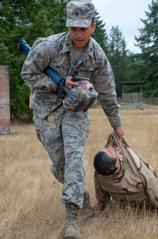 U.S. Air Force Maj. Vinay Gupta moves a simulated casualty during a tactical combat casualty care (TCCC) class for exercise Tropic Halo 2019 at Joint Base Lewis-McChord in Tacoma, Wash., Aug. 7, 2019. Tropic Halo is designed to enhance Operational Hospital Support Unit Bremerton's medical and mission capabilities on several levels: increase TCCC and trauma nurse core course readiness rates while minimizing overall training costs; promote intra-service cohesion with collaborative training in a joint service environment and leverage Navy and Air Force command assets to generate better training opportunities. (U.S. Navy photo by Mass Communication Specialist 1st Class Ryan Riley)