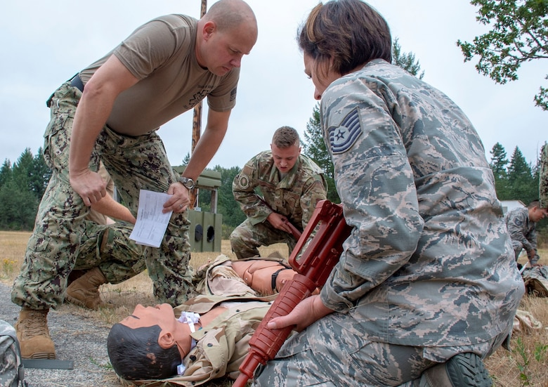Hospital Corpsman 1st Class Rob Johnston, an instructor assigned to Navy Reserve Navy Medicine Education and Training Command and selected for the rank of chief, evaluates U.S. Air Force Tech Sgt. Kristin Trujeque tending to a simulated casualty during a tactical combat casualty care (TCCC) class for exercise Tropic Halo 2019 at Joint Base Lewis-McChord in Tacoma, Wash., Aug. 7, 2019. Tropic Halo is designed to enhance Operational Hospital Support Unit Bremerton's medical and mission capabilities on several levels: increase TCCC and trauma nurse core course readiness rates while minimizing overall training costs; promote intra-service cohesion with collaborative training in a joint service environment and leverage Navy and Air Force command assets to generate better training opportunities. (U.S. Navy photo by Mass Communication Specialist 1st Class Ryan Riley)