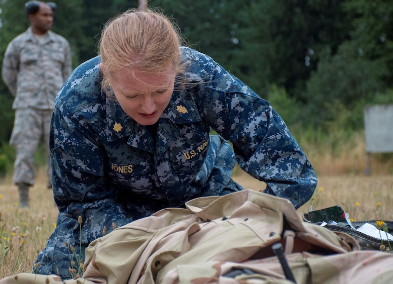 Lt. Cmdr. Katie Jones, assigned to Operational Hospital Support Unit Bremerton, tends to a simulated casualty during a tactical combat casualty care (TCCC) class for exercise Tropic Halo 2019 at Joint Base Lewis-McChord in Tacoma, Wash., Aug. 7, 2019. Tropic Halo is designed to enhance Operational Hospital Support Unit Bremerton's medical and mission capabilities on several levels: increase TCCC and trauma nurse core course readiness rates while minimizing overall training costs; promote intra-service cohesion with collaborative training in a joint service environment and leverage Navy and Air Force command assets to generate better training opportunities. (U.S. Navy photo by Mass Communication Specialist 1st Class Ryan Riley)