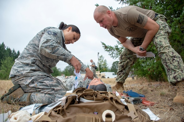 Hospital Corpsman 1st Class Rob Johnston, an instructor assigned to Navy Reserve Navy Medicine Education and Training Command and selected for the rank of chief, evaluates U.S. Air Force Staff Sgt. Mariela Rodriguez tending to a simulated casualty during a tactical combat casualty care (TCCC) class for exercise Tropic Halo 2019 at Joint Base Lewis-McChord in Tacoma, Wash., Aug. 7, 2019. Tropic Halo is designed to enhance Operational Hospital Support Unit Bremerton's medical and mission capabilities on several levels: increase TCCC and trauma nurse core course readiness rates while minimizing overall training costs; promote intra-service cohesion with collaborative training in a joint service environment and leverage Navy and Air Force command assets to generate better training opportunities. (U.S. Navy photo by Mass Communication Specialist 1st Class Ryan Riley)