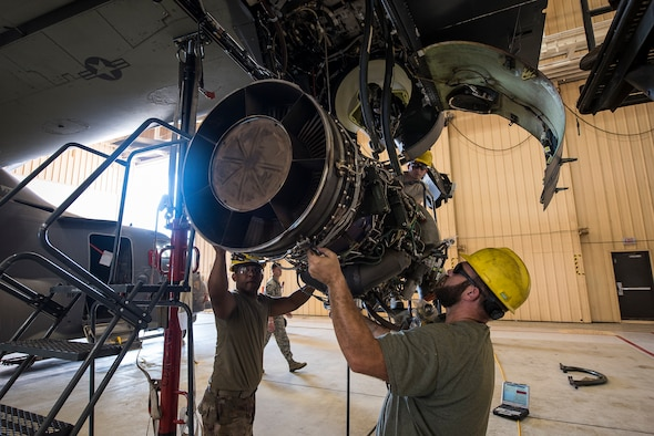 Airman 1st Class Omar Rodriguez, 727th Special Operations Aircraft Maintenance Squadron crew chief, and Luke McSweeney, 727 SOAMXS contract maintainer, guide a CV-22 Osprey engine into the aircraft as it is hoisted at Cannon Air Force Base, N.M, Aug. 13, 2019. The process of replacing the engine took the team of three 25 minutes. (U.S. Air Force Photo by Senior Airman Vernon R. Walter III)