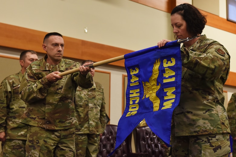 Lt. Col. Stephen Boglarski, 341st Healthcare Operations Squadron commander, left, and Master Sergeant Kimberly Severyn, 341st HCOS superintendent, unfurl the HCOS guidon August 16, 2019, at the Grizzly Bend on Malmstrom Air Force Base, Mont.