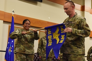Lt. Col. Michelle Dimoff, 341st Operational Medical Readiness Squadron commander, left, and Master Sergeant Derrick Rutherford, 341st OMRS superintendent, unfurl the OMRS guidon August 16, 2019, at the Grizzly Bend on Malmstrom Air Force Base, Mont.