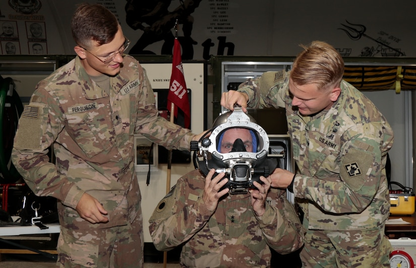 """Maj. Gen. Gordon L. Ellis, center, 38th Infantry Division commanding general, dons a diver mask with the help of 511th Engineer Dive Detachment soldiers, Spc. Kyle Ferguson and Capt. Chase Olson, at Kuwait Naval Base, Tuesday, Aug. 13, 2019. """"Our biggest importance to Task Force Spartan is support restoring expeditionary logistical support routes,"""" said Olson."""