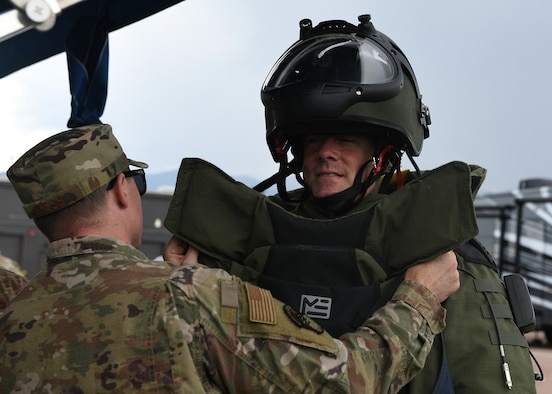 Staff Sgt. Lawrence Gress, 21st Civil Engineer Squadron explosive ordnance disposal technician, left, helps Col. Thomas Falzarano, 21st Space Wing commander, get into a bomb suit Aug. 7, 2019 on Peterson Air Force Base, Colorado. During a tour of the CES, Falzarano also met the EOD Airmen and participated in a bomb simulation. (U.S. Air Force photo by Airman 1st Class Andrew Bertain)