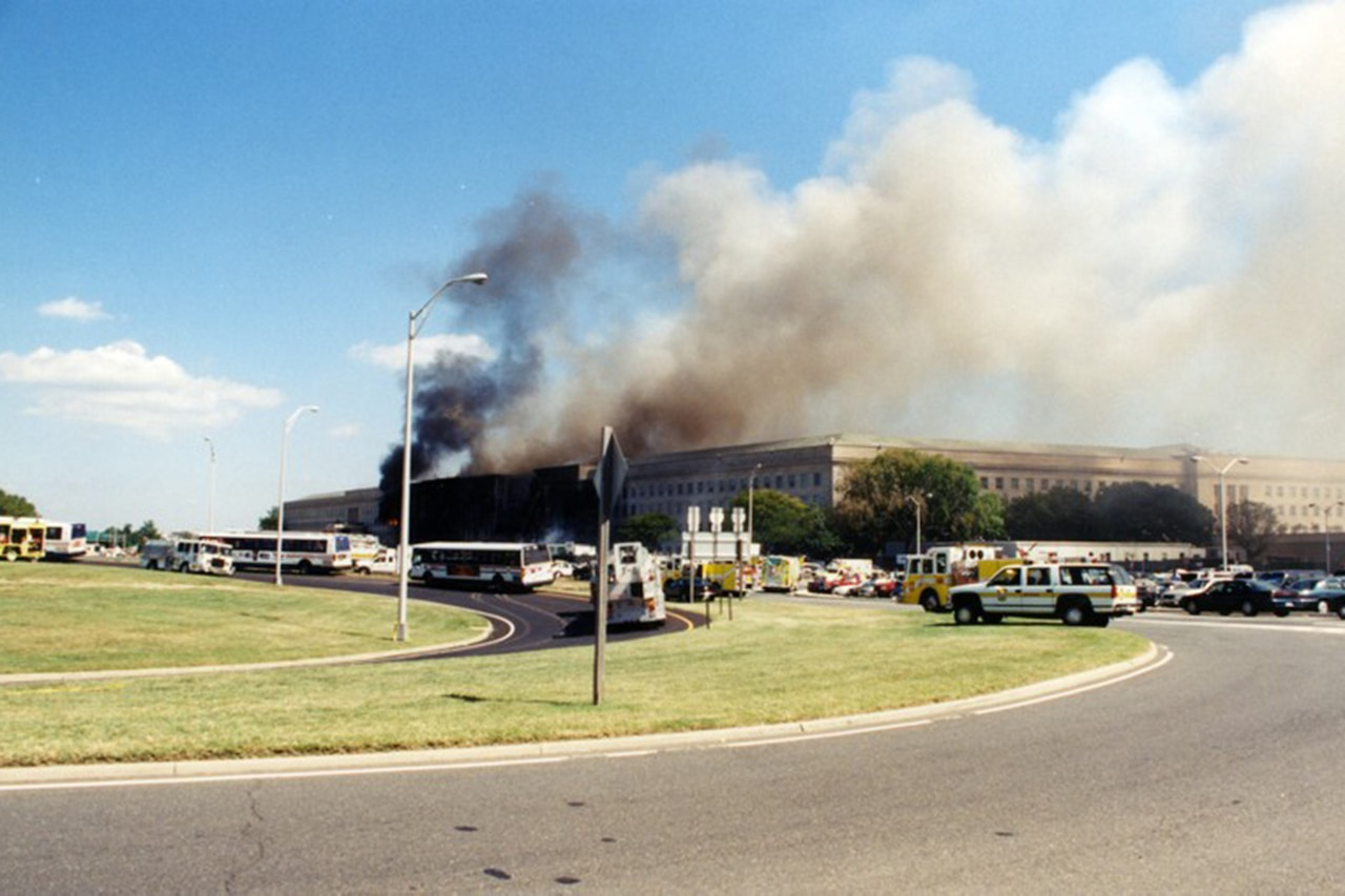 Smoke pours out of the Pentagon as emergency response vehicles surround the building.