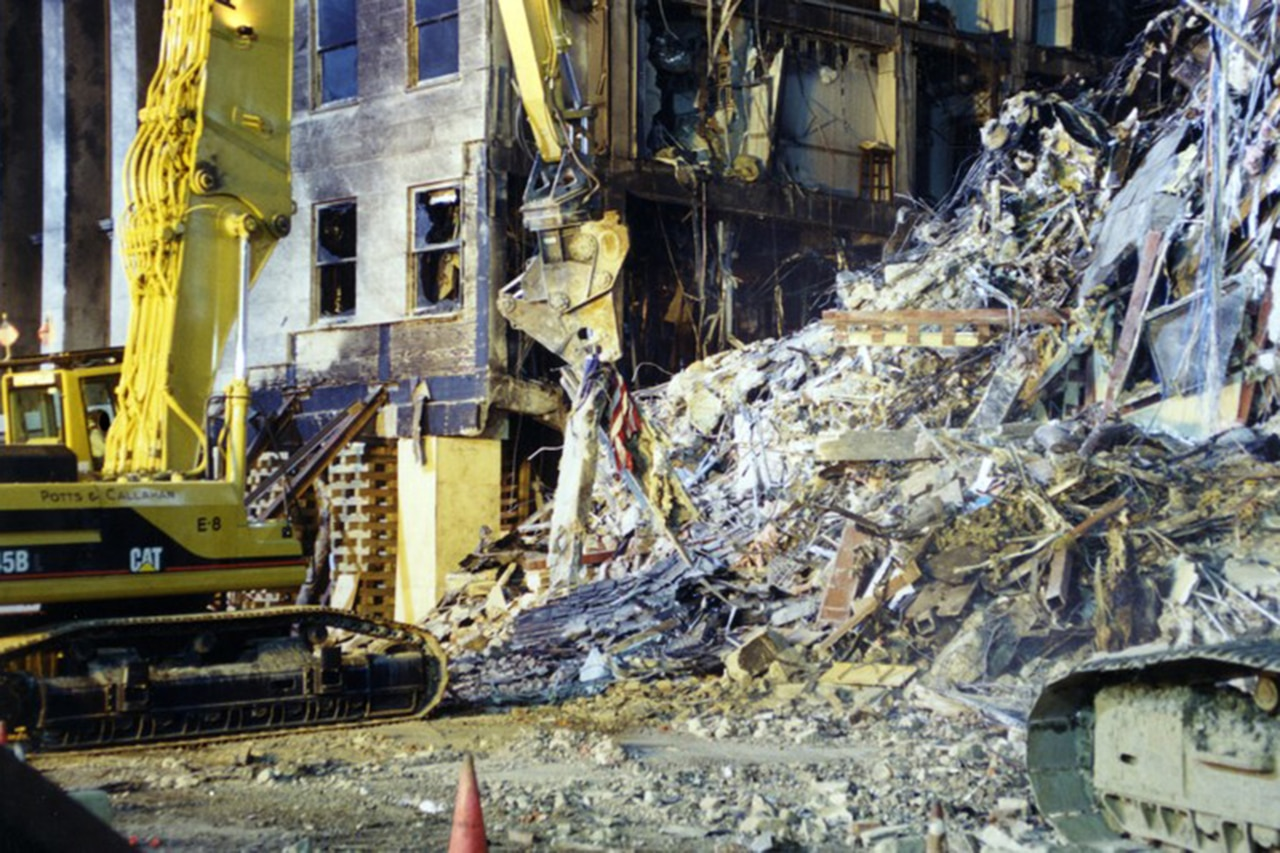 A large machine picks up debris, including an American flag.