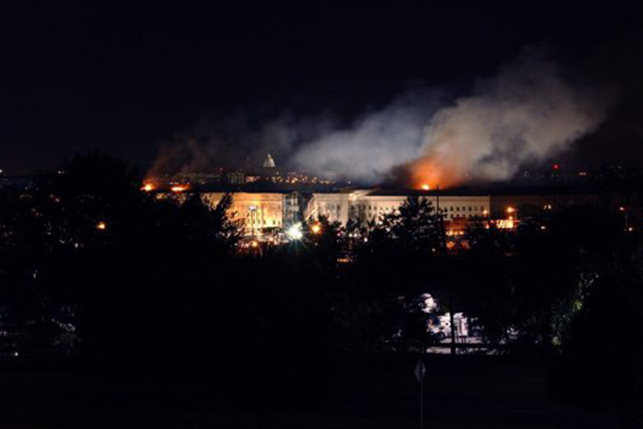A night time shot of a  building in the distance with  smoke and flames coming from it.