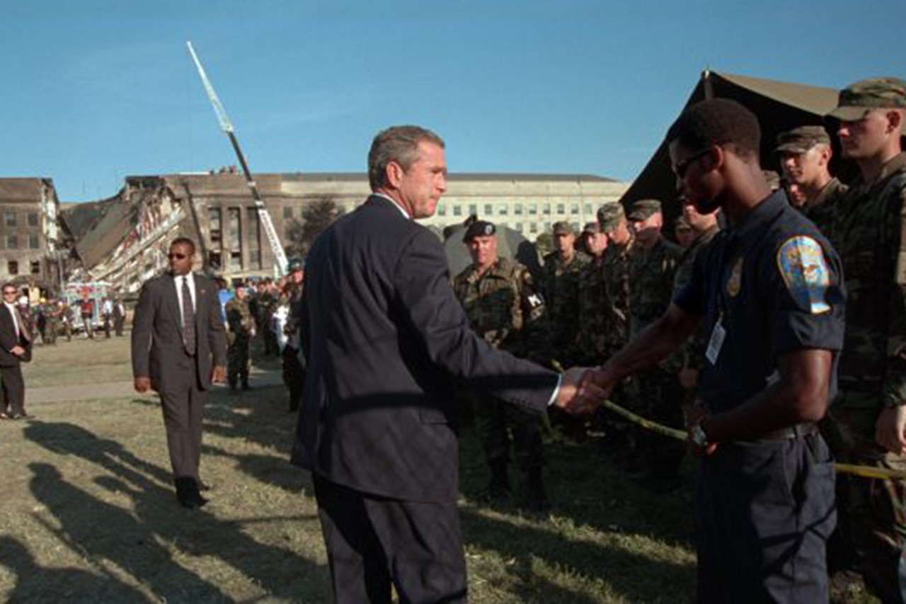 President George W. Bush shakes hands with a man in uniform in front of the falling wall of the Pentagon.