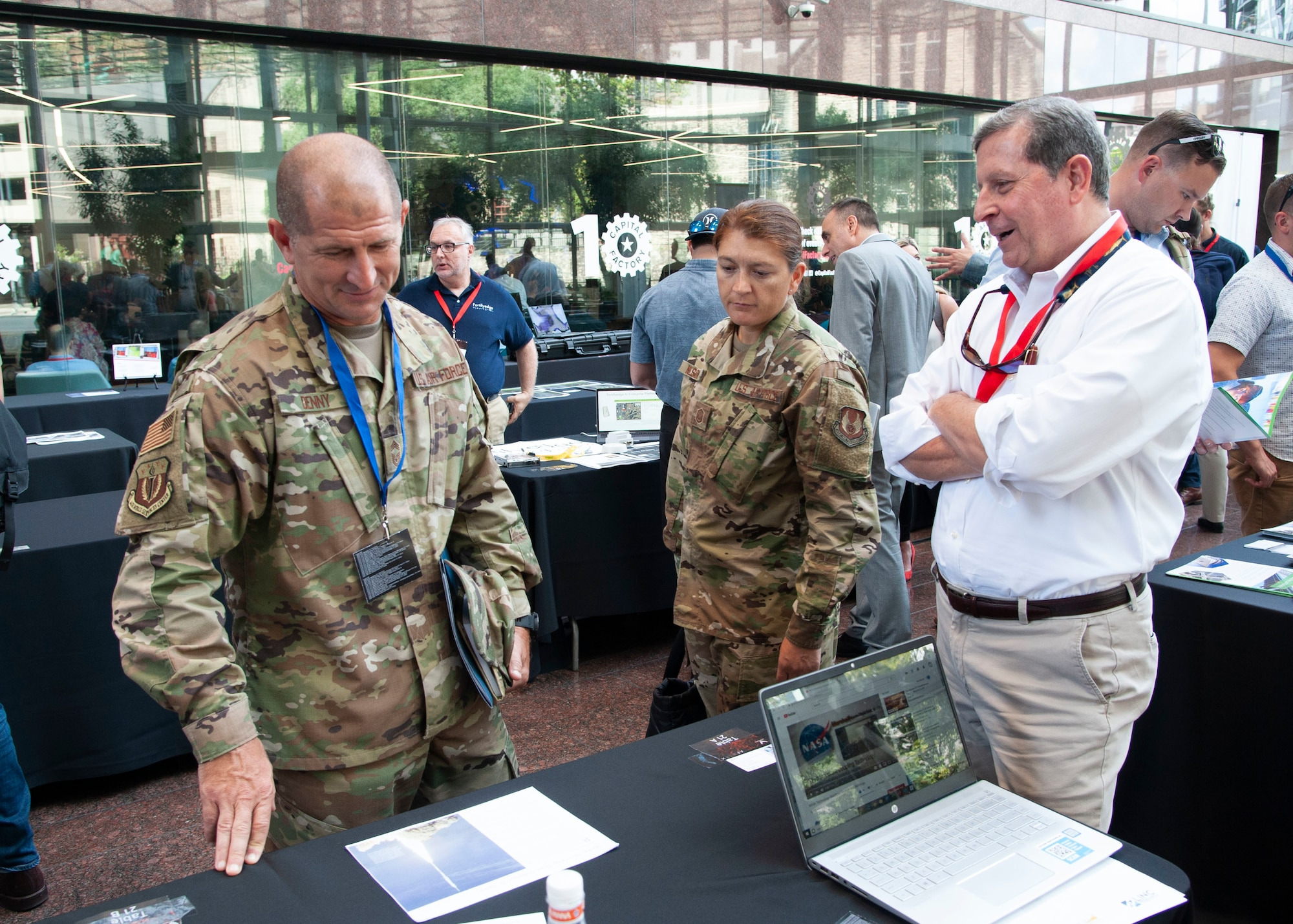 Two Airmen talk with a Phase I Small Business Innovation Research entrepreneur of the program during the first-ever Spark Collider at the AFWERX Austin Hub Aug 14, 2019. The event connected approximately 100 Phase I Small Business Innovation Research companies and Airmen from about 50 bases to potentially solve Air Force problem areas. (U.S. Air Force courtesy photo)