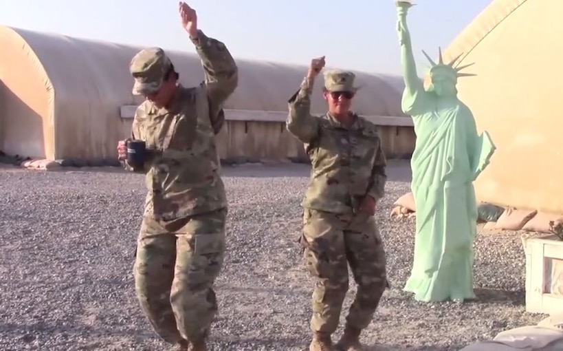 A deployed service members dances while a family dances on the other side of the screen.