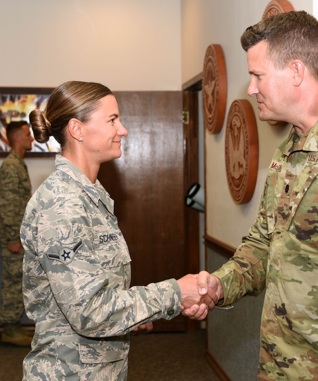 U.S. Air Force Lt. Col. Michael McCourt, 312th Training Squadron commander, congratulates Airman Kristina Schneider, 312th Training Squadron fire protection student during her graduation at the Louis F. Garland Department of Defense Fire Academy on Goodfellow Air Force Base, Texas, August 20, 2019. Schneider successfully finished a 20-day fire suppression course where students learn with a hands on approach to a variety of burning environments, such as vehicle, ground, and building fires. (U.S. Air Force photo by Airman 1st Class Abbey Rieves/Released)