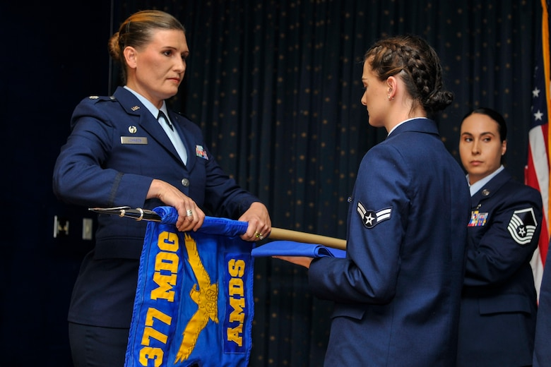 Lt. Col. Leigh Johnson, 377th Aerospace Medicine Squadron commander, furls the squadron guidon in a redesignation ceremony at Kirtland Air Force Base, N.M., August 16, 2019. The 377th Operational Medical Readiness Squadron will provide care for active duty service members while the 377th Healthcare Operations Squadron will provide care for non-active duty personnel. (U.S. Air Force photo by Airman 1st Class Austin J. Prisbrey)