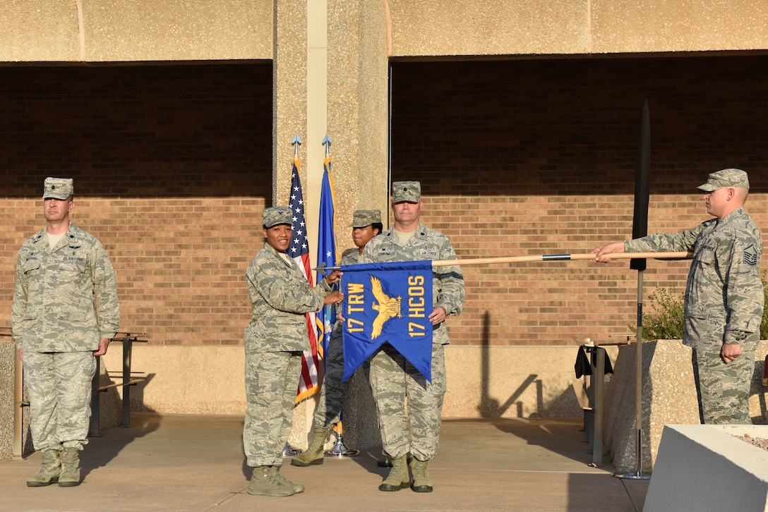 U.S. Air Force Lt. Col. Warren Conrow, 17th Healthcare Operations Squadron commander, and Col. Lauren Byrd, 17th Medical Group commander, unfurl the new guidon signifying the inactivation of the 17th Medical Support Squadron and the activation of the 17th HCOS during the reorganization ceremony at the Ross Clinic on Goodfellow Air Force Base, Texas, August 15, 2019. The guidons are retired, not destroyed, and the new guidons were activated to represent the squadrons. (U.S. Air Force photo by Senior Airman Seraiah Wolf/Released)