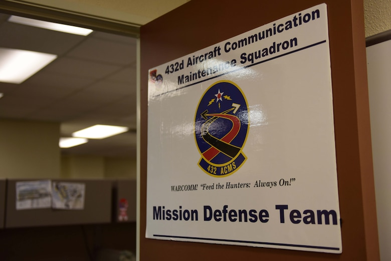 A Mission Defense Team sign hangs inside the 432nd Aircraft Communications Maintenance Squadron building at Creech Air Force Base, Nevada, April 29, 2019. MDTs are the result of the Cyber Squadron Initiative (CS-I), which is a plan to move communications squadrons away from Information Technology (IT) service and toward a mission set that involves the cyberspace side of their wing's operational mission. (U.S. Air Force photo by Airman 1st Class Haley Stevens)
