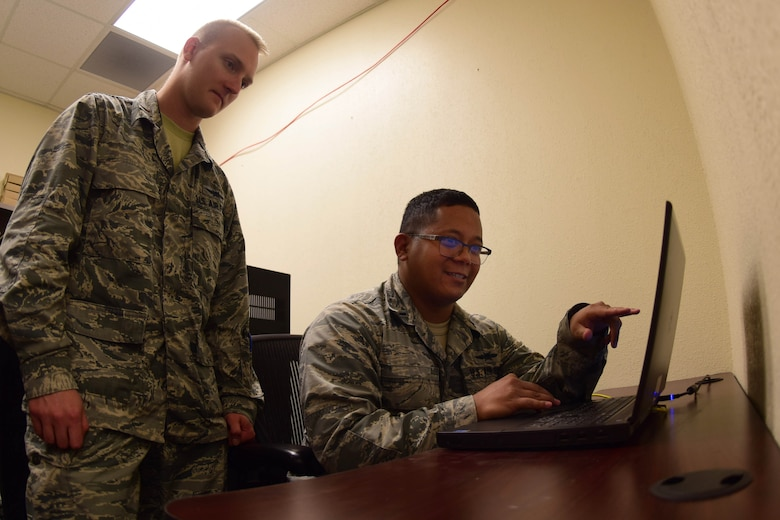 1st Lt. Vaughn, 432nd Aircraft Communications Maintenance Squadron Mission Defense Team officer in charge, and 2nd Lt. Eric, 432nd ACMS MDT Assistant officer in charge, go over computer code at Creech Air Force Base, Nevada, April 29, 2019. The 432nd Wing's MDT is tasked with assuring the integrity of the MQ-9 Reaper's cyber networks and protecting the support equipment that connect the aircraft to the cockpits on the ground. (U.S. Air Force photo by Airman 1st Class Haley Stevens)