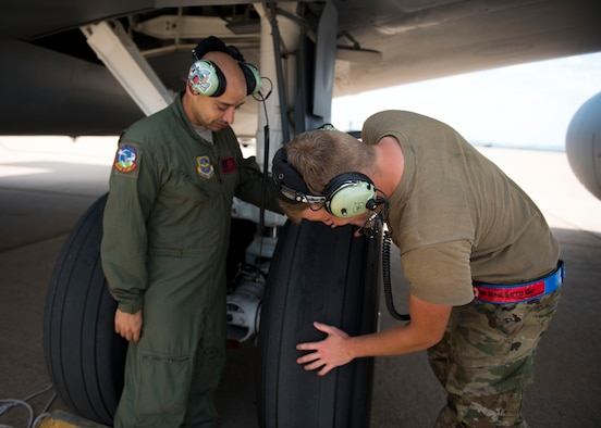 U.S. Air Force Tech. Sgt. Norbert Roland (left) and Senior Airman Zachery Murray (right), 92nd Aircraft Maintenance Squadron flying crew chiefs, examine landing gear during pre-flight checks on a KC-135 Stratotanker at Dyess Air Force Base, Texas, Aug. 13, 2019.