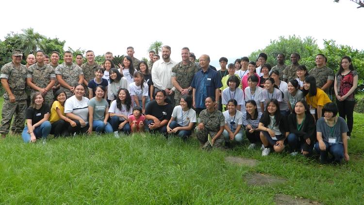 沖縄県うるま市役所と米海兵隊基地キャンプ・コートニーの交流事業の一環で、市内の高校生を対象にした夏季英語クラスが8月19日に基地内で始まり、トーマス・レーリー基地ディレクター(左)、マシュー・ネーション基地司令官(中)、島袋俊夫うるま市長(右)も出席し、参加者全員での集合写真。