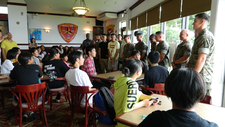 高校生のための夏季英語クラスにボランティアで集まった海兵隊員を高校生たちに紹介。沖縄県うるま市役所と米海兵隊基地キャンプ・コートニーの交流事業の一環で、市内の高校生を対象にした夏季英語クラスが月曜日に始まり、基地内で行われるクラスで1週間を通して高校生たちのコミュニケーション能力の向上を図ります。