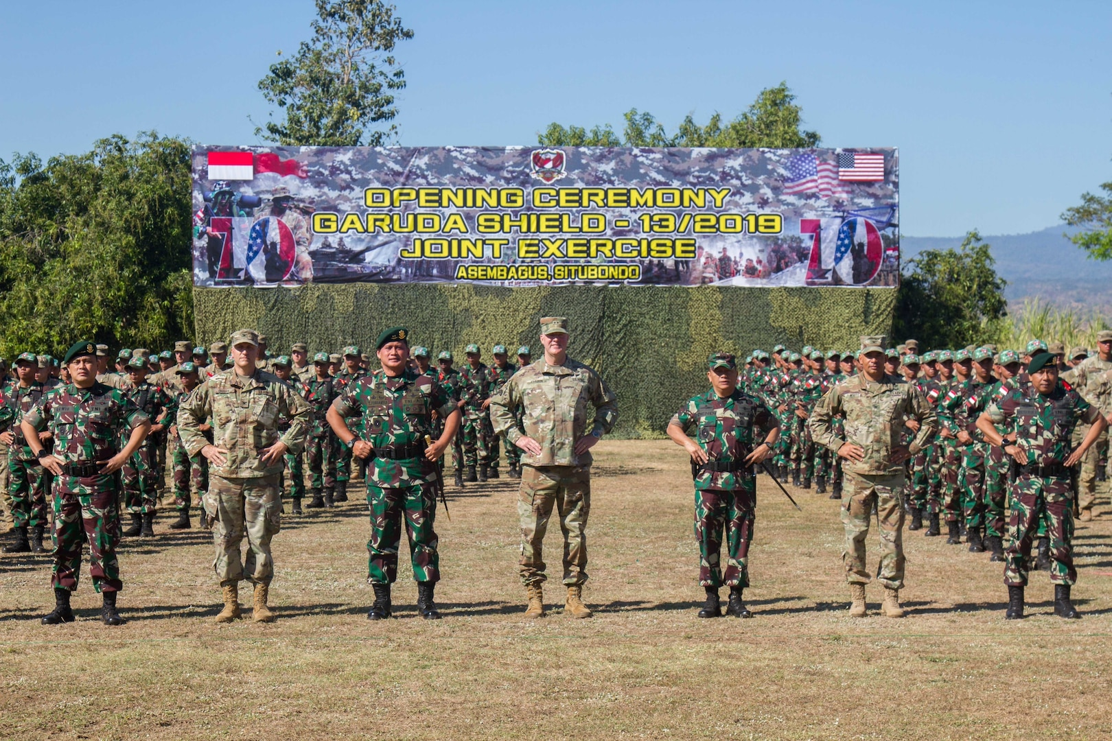 The 2019 Garuda Shield leaders from both armies pose for a picture with a formation of U.S. and Indonesian forces during the 2019 Garuda Shield opening ceremony Aug. 19, 2019, at Dodiklatpur, Indonesia. Garuda Shield is an annual, bilateral military partnership sponsored by the U.S. Army Pacific and hosted annually by Tentara Nasional Indonesia. (U.S. Army photo by Pfc. Ezra Camarena, 28th Public Affairs Detachment)
