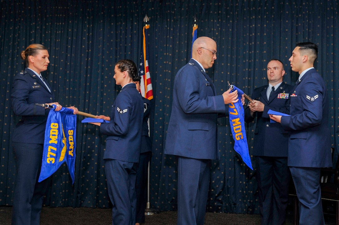 Guidons belonging to the 377th Aerospace Medicine Squadron and the 377th Medical Operations Squadron are furled in a redesignation ceremony at Kirtland Air Force Base, N.M., August 16, 2019. The 377th Aerospace Medicine Squadron and the 377th Medical Operations Squadron were redesignated to the 377th Operational Medical Readiness Squadron and the 377th Health Care Operations Squadron. (U.S. Air Force photo by Airman 1st Class Austin J. Prisbrey)