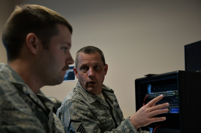 Members of the Mission Defense Team at the 432nd Aircraft Communications Maintenance Squadron discuss a simulated cyber-attack during a cyber-defense training exercise at Creech Air Force Base, Nevada, Dec. 21, 2017. The Air Combat Command selected the 432nd ACMS to test the possibilities of the Cyber Squadron Initiative (CS-I) by defending the Remotely Piloted Aircraft network. (U.S. Air Force photo by Airman 1st Class Haley Stevens)