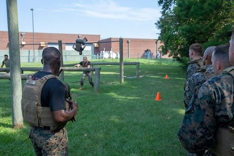 U.S. Marine Corps Martial Arts Instructor trainers with 1st Battalion, 10th Marine Regiment Battery C, 2nd Marine Division, demonstrate proper obstacle course navigation to students of a Martial Arts Instructor Course at Camp Lejeune, N.C., Aug. 14, 2019. This three-week long course trains Marines to become Marine Corps Martial Arts Instructors. (U.S. Marine Corps photo by Cpl. Caleb T. Maher)