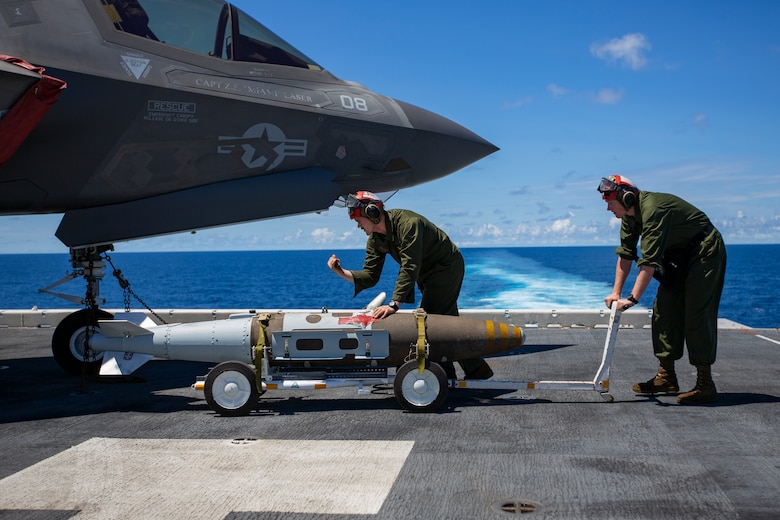 Ordnance Marines with Marine Medium Tiltrotor Squadron 265, 31st Marine Expeditionary Unit, prepare to load a Joint Direct Attack Munition onto an F-35B Lightning II fighter aircraft, aboard the amphibious assault ship USS Wasp, Pacific Ocean, August 7, 2019. Wasp, flagship of the Wasp Amphibious Ready Group, with embarked 31st MEU, is operating in the Indo-Pacific region to enhance interoperability with partners and serve as ready-response force for any type of contingency, while simultaneously providing a flexible and lethal crisis response force ready to perform a wide range of military operations.