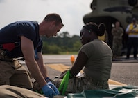 Brian Yohn, 733d Civil Engineer Division firefighter, checks a patient's status during an aircraft crash exercise at Joint Base Langley-Eustis, Virginia, Aug. 13, 2019.