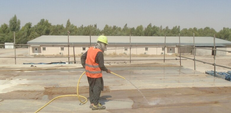 Local National employee sprays water in the curing process of the concrete roof slab.