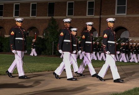 Marines with the noncommissioned officer parade marching staff, Marine Barracks Washington, D.C., march across Center Walk during the Noncommissioned Officer Friday Evening Parade at Marine Barracks Washington, D.C., Aug. 16, 2019. The hosting official for the evening was Lt. Gen. John J. Broadmeadow, director of Marine Corps Staff and the Under Secretary of the Navy, the Honorable Mr. Thomas B. Modly, was the guest of honor. (U.S. Marine Corps photo by Sgt. Robert Knapp/Released)