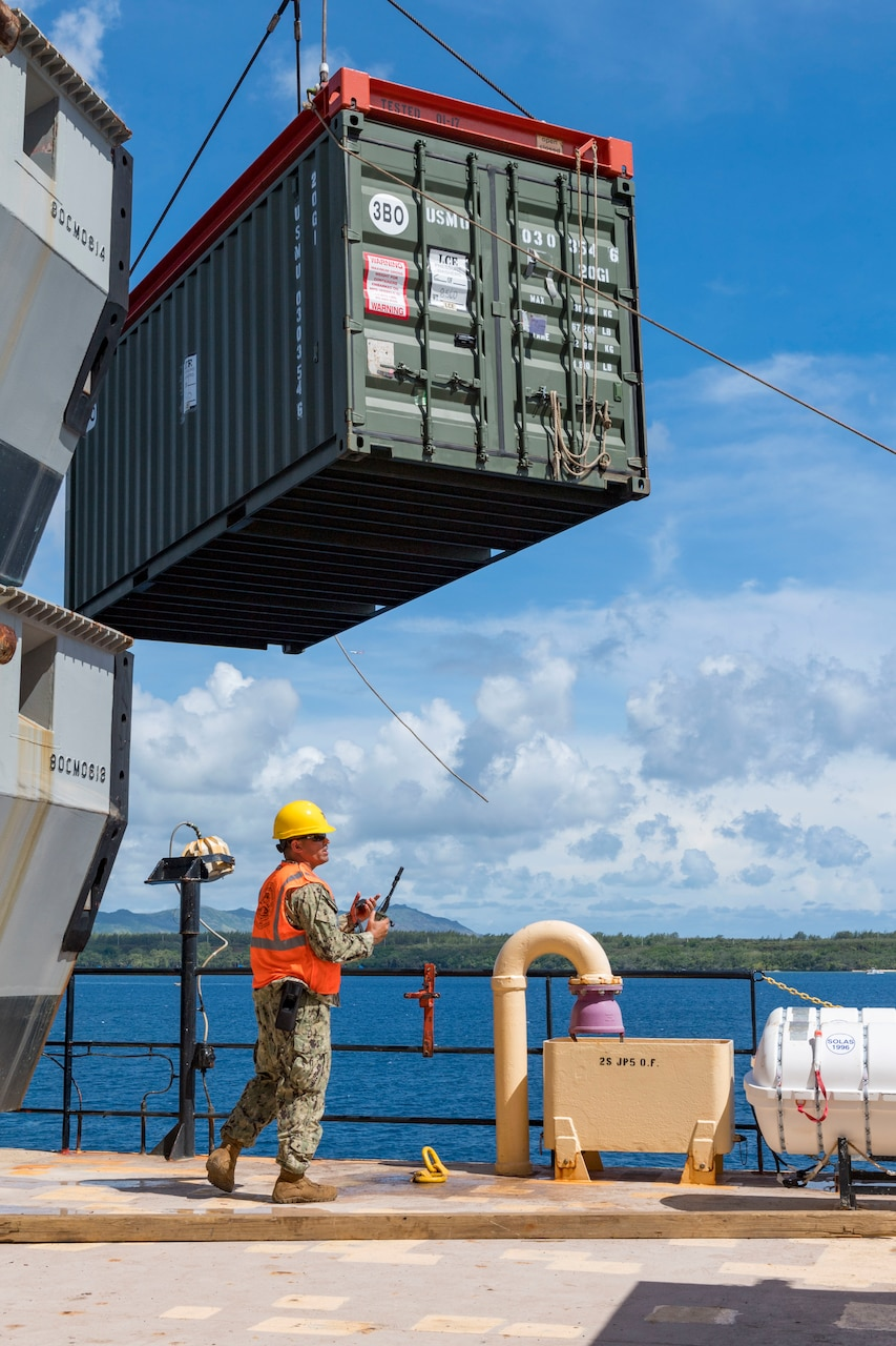 A man in military uniform wears a hard hat and carries a portable radio.  Above him is a cargo container suspended from a crane.