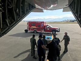 Coast Guard Air Station Kodiak HC-130J Hercules aircrew helps to complete a long-range medical evacuation of two people to Anchorage on Aug. 3, 2019.