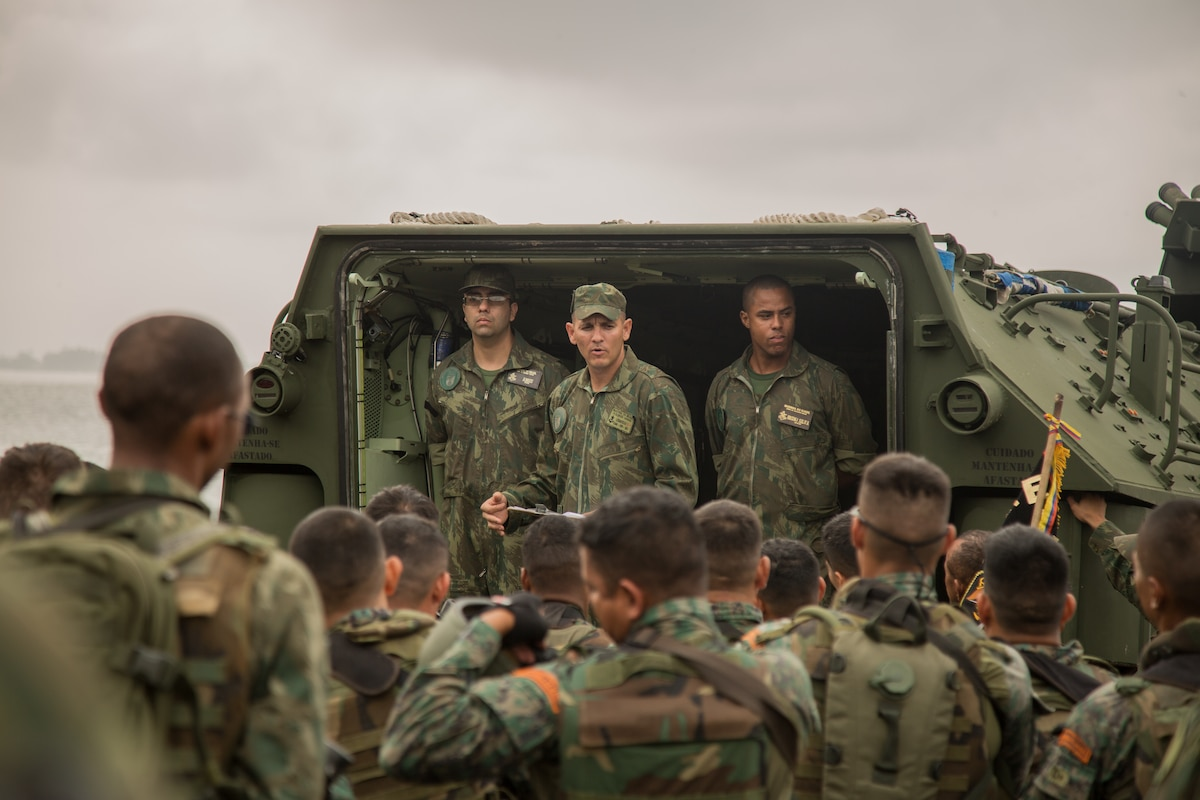 A military leader gives a safety brief to a group of troops.