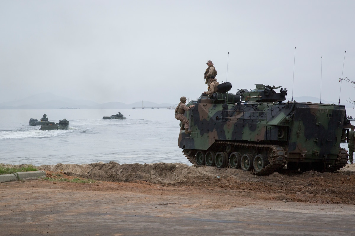Marine amphibious assault vehicles come ashore.