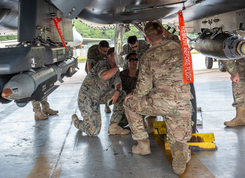 Staff Sgt. Ryan Carel, 4th Civil Engineer Squadron explosive ordnance disposal technician, shows U.S. Marine EOD technicians how to safely pin landing gear on an F-15E Strike Eagle, August 14, 2019, at Seymour Johnson Air Force Base, North Carolina. The Marines, assigned to the 8th Engineer Support Battalion, 2nd Marine Logistics Group, came to Seymour Johnson AFB to become familiar with aircraft weaponry. (U.S. Air Force photo by Senior Airman Kenneth Boyton)