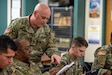 Sgt. 1st Class Thomas Flannery, engages with Sgt. 1st Class Alexander Barrios during an active learning exercise where students apply what they have learned during the information technology course.