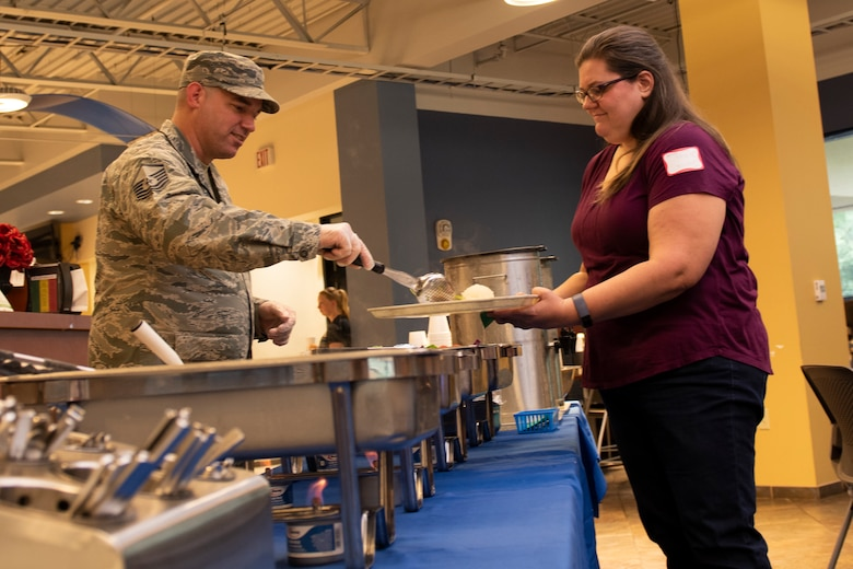 Master Sgt. Kianta Asplund, left, 23d Force Support Squadron NCO in charge of readiness, serves food to a participant during a Deployed Spouse's Dinner Aug. 20, 2019, at Moody Air Force Base, Ga.  The dinner served as an opportunity for the families of deployed members to bond and provide relief. The mission's success depends on resilient Airmen and families, who are prepared to make sacrifices with the support of their fellow Airmen, local communities and leadership. (U.S. Air Force photo by Airman Elijah M. Dority)