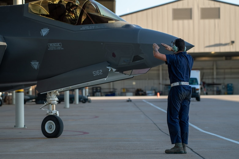 A crew chief with the 388th Fighter Wing marshals an F-35A prior to take off from Hill Air Force Base, Utah, the evening of Aug. 20, 2019, as the active duty 388th and reserve 419th Fighter Wings conducted local night flying operations. The wings are required to train at night to maintain their readiness and all-weather capabilities. Increased flying also provides a valuable opportunity to evaluate aircraft maintenance resiliency and operational agility. (U.S. Air Force photo by R. Nial Bradshaw)