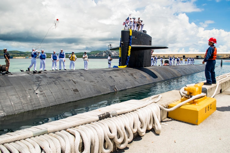 Sailors stand on top of a submarine as it is near a pier.