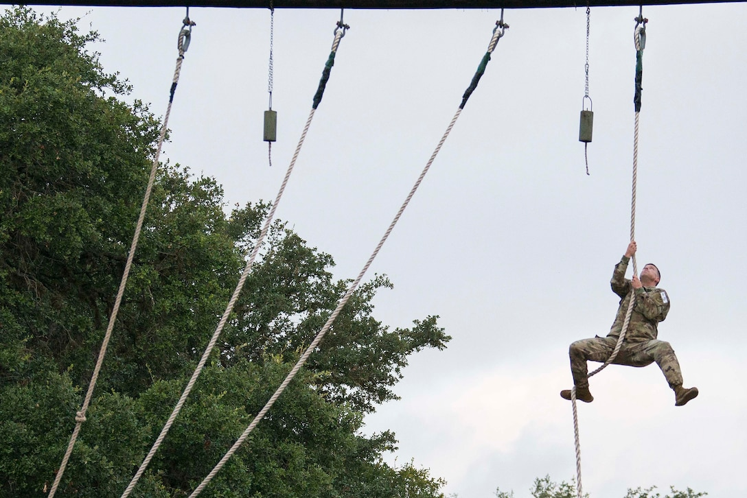 A soldier climbs a rope.