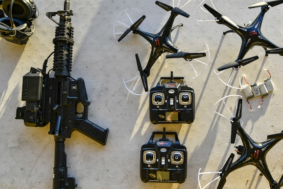 A M4 Carbine rifle donning the Smart Shooter sighting device lays next to drones that will be used as moving targets for 9th Reconnaissance Wing leadership at Beale Air Force Base, California, Aug. 14, 2019. The sighting device attaches to the weapon and locks on then fires to neutralize its target with or without movement. The device is also being used to limit friendly fire as the weapon cannot be fired unless it is purposely locked on. (U.S. Air Force photo by Tech. Sgt. Alexandre Montes)