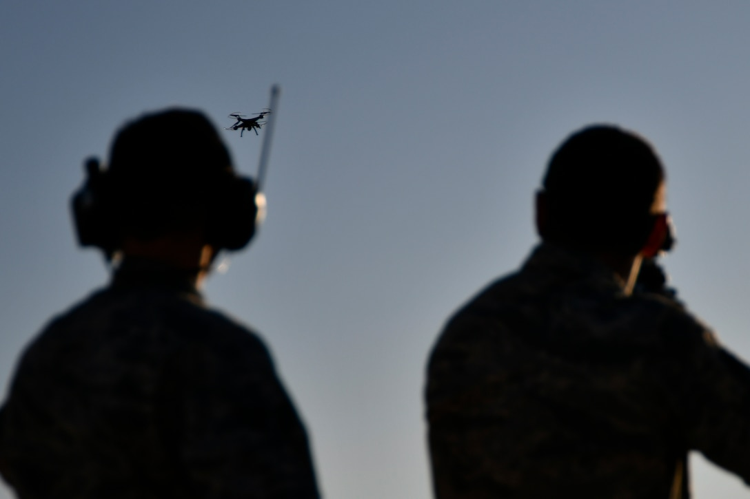 Staff Sgt. Colton Becker, 9th Security Forces Squadron training flight, controls a drone takeoff while Chief Master Sgt. Dustin Hall, 9th Reconnaissance Wing command chief, charges his weapon and sets his sights using the Smart Shooter sighting device during a demonstration at Beale Air Force Base, California, Aug. 14, 2019. The 9th SFS Airmen have been using off the shelf commercial technology to help train and improve how their missions are conducted to protect the installation. (U.S. Air Force photo by Tech. Sgt. Alexandre Montes)