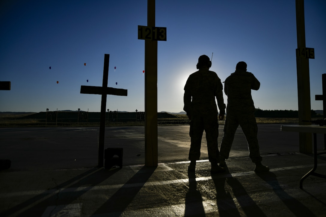 Two airmen silhouetted as they stand near some cross-shaped posts, with airborne drones in the sky.