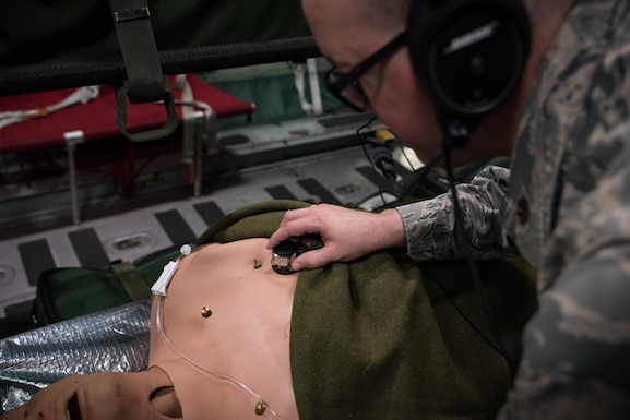 While testing the new wireless high-noise filtering stethoscope, Maj. Daniel Bevington, a nurse researcher in the 711th Human Performance Wing of the Air Force Research Laboratory, places the device on a mannequin's chest to listen to internal sounds. (U.S. Air Force photo/Richard Eldridge)